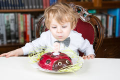 Little boy celebrating third birthday and blowing off  candles Stock Image