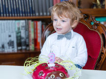 Little boy celebrating third birthday and blowing off  candles Stock Photo