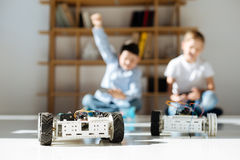 Little boy celebrating victory in a racing game. Pleasant victory. The focus being on two robotic vehicles standing on the floor while to boys controlling them Royalty Free Stock Photos