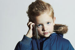 Little boy with cellphone. modern child in winter coat. fashion kids.children Royalty Free Stock Images