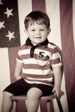 Little boy on chair with flag Royalty Free Stock Photography