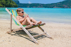 A little boy in chaise longue against  sea drinking juice Royalty Free Stock Image