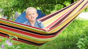 Little Boy with charming Smile in hammock stock video