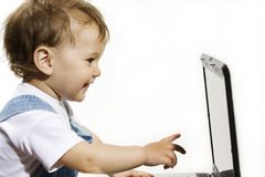 Little Boy che esamina lo schermo del computer portatile Immagini Stock