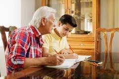 Little Boy che fa compito della scuola con l'uomo anziano a casa Fotografie Stock Libere da Diritti
