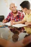 Little Boy che fa compito della scuola con l'uomo anziano a casa Immagine Stock