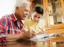 Little Boy che fa compito della scuola con l'uomo anziano a casa Fotografia Stock