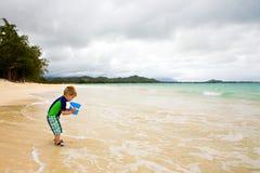 Little Boy che gioca con una benna sulla spiaggia Fotografia Stock