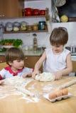 Little Boy che guarda suo fratello gemello While Kneading Dough per la pizza sul tavolo da cucina Immagine Stock Libera da Diritti