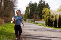 Little Boy che prende disordine sul bordo della strada Fotografia Stock