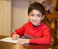 Little Boy che si siede ad una Tabella e che fa il suo compito Fotografia Stock Libera da Diritti