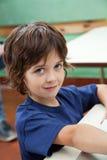 Little Boy che sorride allo scrittorio Immagini Stock Libere da Diritti
