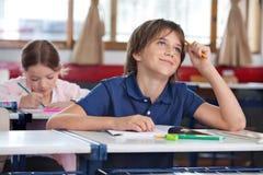 Little Boy che sorride mentre cercando nell'aula Fotografie Stock