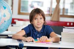Little Boy che sorride mentre sedendosi con il globo e Fotografia Stock Libera da Diritti