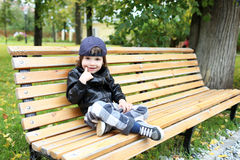 Little boy in in checkered pants and a leather jacket sits on th Royalty Free Stock Images