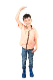 Little boy checking his height isolate on white background Royalty Free Stock Photo