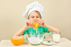 Little boy in chef hat pours egg for baking cake Royalty Free Stock Photography