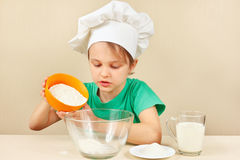 Little boy in chef hat pours flour for baking cake Royalty Free Stock Photo
