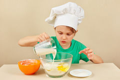 Little boy in chef hat pours milk for baking cake Stock Photos
