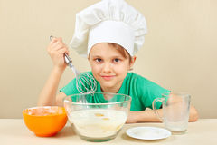 Little boy in chef hat prepares the dough for baking cake Royalty Free Stock Images