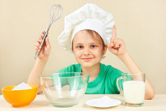 Little boy in chef hat at the table with ingredients is going to cook cake Royalty Free Stock Photos