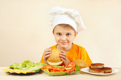 Little boy in chef hat at the table with ingredients is going to cook hamburger Royalty Free Stock Images