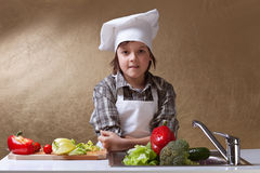 Little boy with chef hat washing vegetables Stock Images