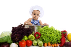 Little boy in chef's hat sitting in pot with vegetables Stock Images