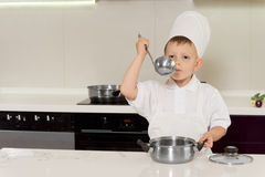 Little boy chef tasting his recipe Stock Photo