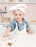 Little boy chef is tucked away on a table Stock Photos