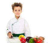 Little boy chef in uniform. Little happy boy chef in uniform with knife cutting vegetables isolated on white Stock Photo