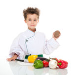 Little boy chef in uniform. Little happy boy chef in uniform with knife cooking vegatables holding potato isolated on white Stock Photography
