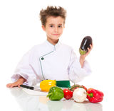 Little boy chef in uniform. Little happy boy chef in uniform with knife cooking vegatables holding aubergine isolated on white Stock Photography