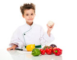 Little boy chef in uniform. Little happy boy chef in uniform with knife cooking vegatables holding onion isolated on white Stock Images