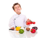 Little boy chef in uniform. Little happy boy chef in uniform with knife cooking vegatables holding bunch of tomatoes isolated on white Royalty Free Stock Image