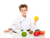 Little boy chef in uniform. Little happy boy chef in uniform with knife cooking vegatables holding yellow paprika isolated on white Royalty Free Stock Images