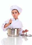 Little boy chef in uniform. With ladle stiring in the pot isolated on white Royalty Free Stock Photo