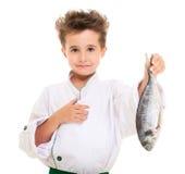 Little boy chef in uniform. Presenting  dorado fish isolated on white Royalty Free Stock Photo