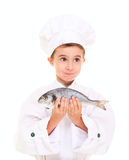 Little boy chef in uniform. Surprised holding dorado fish isolated on white Stock Images