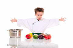 Little boy chef in uniform cooking stock photography
