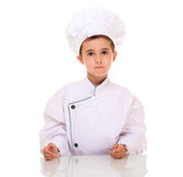 Little boy chef in uniform looking. At camera isolated on white Royalty Free Stock Image