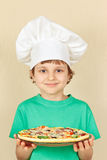 Little boy in chefs hat with cooked homemade pizza Royalty Free Stock Photos