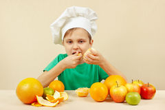 Little boy in chefs hat eat fresh orange at table with fruits Stock Photography