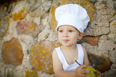 Little boy with chefs hat eats apple Stock Photos