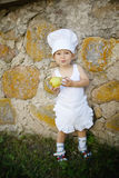 Little boy with chefs hat eats apple Stock Photo