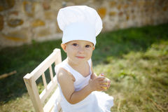 Little boy with chefs hat eats apple Royalty Free Stock Photography