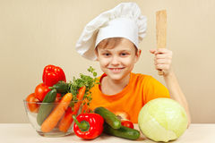 Little boy in chefs hat with fresh vegetables at table Stock Images