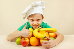 Little boy in chefs hat with fruits at table Stock Photos