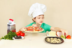 Little boy in chefs hat puts the ingredients on pizza crust Stock Images