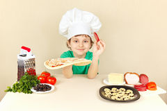 Little boy in chefs hat puts sausage on pizza crust Royalty Free Stock Photo